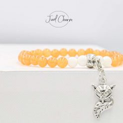 Handmade orange Agate and white coral gemstone bracelet shown with a fox charm